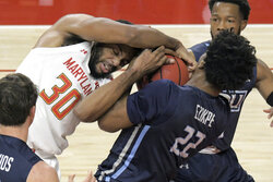 Maryland forward Galin Smith (30) tangles with Old Dominion forward Kalu Ezikpe (22) over a rebound during the first half during the first half of an NCAA college basketball game in College Park, Md., Wednesday, Nov. 25, 2020. (Karl Merton Ferron/The Baltimore Sun via AP)
