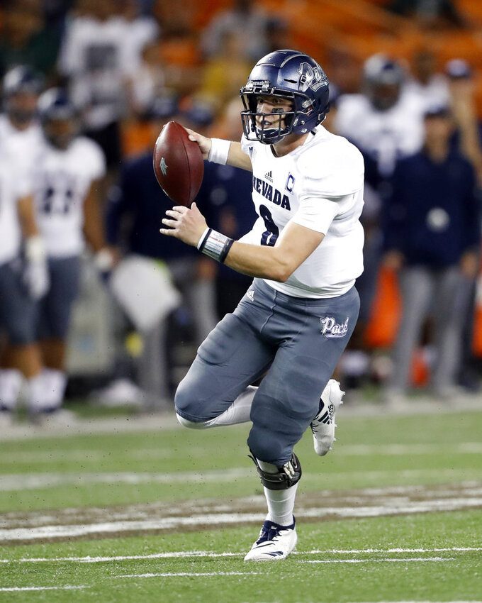 Nevada quarterback Kaymen Cureton (8) runs for yards against Hawaii during the second quarter of an NCAA college football game, Saturday, Oct. 20, 2018, in Honolulu. (AP Photo/Marco Garcia)