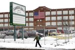 FILE - In this Jan. 17, 2013, photo, a man walks past the Remington Arms Company in Ilion, N.Y.  The firearms company Remington Arms has filed for Chapter 11 bankruptcy protection, Tuesday, July 28, 2020,  for the second time in a little more than two years, despite a recent surge in gun demand. Remington previously filed for bankruptcy protection in March 2018. The company has estimated liabilities between about $100 million and $500 million and between 1,000 and 5,000 creditors, according to the filing. (AP Photo/Mike Groll)