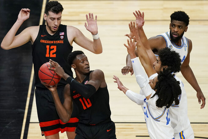 Oregon State's Warith Alatishe (10) looks to pass against UCLA during the first half of an NCAA college basketball game in the quarterfinal round of the Pac-12 men's tournament Thursday, March 11, 2021, in Las Vegas. (AP Photo/John Locher)