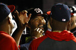 Washington Nationals' Kurt Suzuki, center, high-fives teammates in the dugout after scoring on Asdrubal Cabrera's double in the sixth inning of a baseball game against the Cleveland Indians, Friday, Sept. 27, 2019, in Washington. (AP Photo/Patrick Semansky)