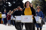 Supporters of Mainers for Health and Parental Rights carry boxes of signed petitions to the Secretary of State's office, Wednesday, Sept. 18, 2019, in Augusta, Maine. The group says they gathered over 92,000 signatures in support of the People's Veto of government-mandated vaccine bill. (AP Photo/Robert F. Bukaty)