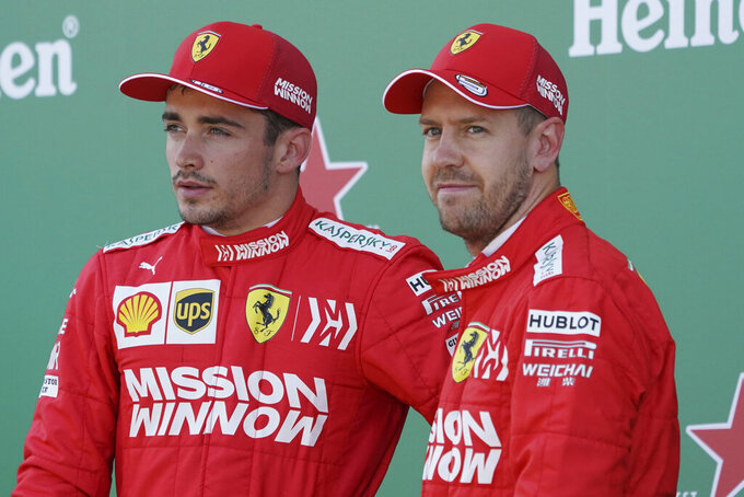 "FILE - In this file photo taken on Oct. 13, 2019, Ferrari driver Sebastian Vettel of Germany stands with teammate Charles Leclerc, left, of Monaco after the qualifying session for the Japanese Formula One Grand Prix at Suzuka Circuit in Suzuka, central Japan. Ferrari team members acknowledged that they need to ""learn from mistakes"" committed last season as they presented their new Formula One car Tuesday. (AP Photo/Toru Hanai)"