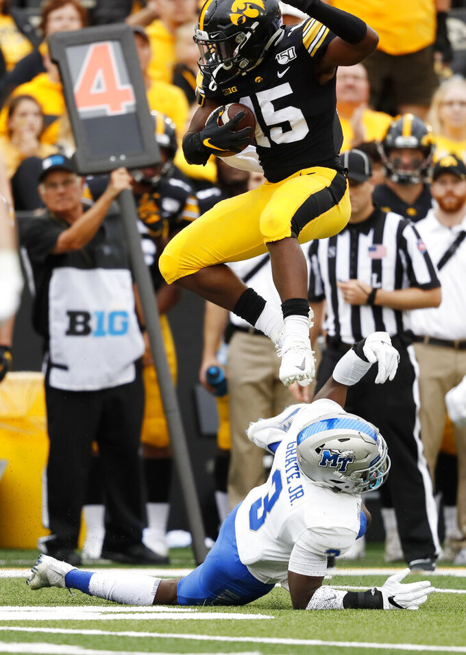 Iowa running back Tyler Goodson (15) leaps over Middle Tennessee safety Gregory Grate Jr. (3) during the second half of an NCAA college football game, Saturday, Sept. 28, 2019, in Iowa City, Iowa. Iowa won 48-3. (AP Photo/Charlie Neibergall)