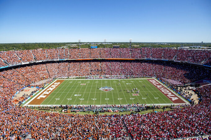 FILE - In this Oct. 12, 2019, file photo, Texas and Oklahoma fans fill the Cotton Bowl during the first half of an NCAA college football game in Dallas. The Texas and Oklahoma college football matchup will be a different game-day atmosphere this year with small crowds, no State Fair, a few food vendors, masks and social distancing. (AP Photo/Jeffrey McWhorter, File)
