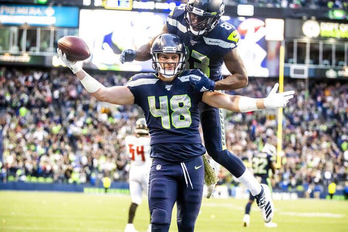 Seahawks tight end Jacob Hollister celebrates after scoring the winning touchdown in overtime with wide receiver David Moore on his back at an NFL football game against the Tampa Bay Buccaneers, Sunday, Nov. 3, 2019, in Seattle. (Mike Siegel/The Seattle Times via AP)
