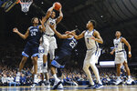 Butler forward Bryce Nze (10) pulls down a rebound between Villanova's Jeremiah Robinson-Earl (24) and Jermaine Samuels (23) during the second half of an NCAA college basketball game in Indianapolis, Wednesday, Feb. 5, 2020. Butler won 79-76. (AP Photo/AJ Mast)