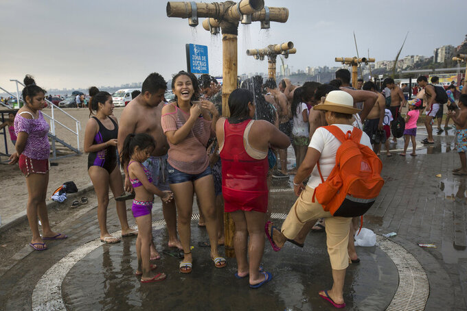 In this Feb. 15, 2020 photo, beachgoers rinse off their bodies of sand and salt after swimming in the Pacific Ocean waters at Agua Dulce beach in Lima, Peru. (AP Photo/Rodrigo Abd)