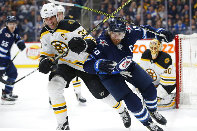 Winnipeg Jets' Blake Wheeler (26) and Boston Bruins' Zdeno Chara (33) chase the puck as goaltender Tuukka Rask (40) watches during the second period of an NHL hockey game Friday, Jan. 31, 2020, in Winnipeg, Manitoba. (John Woods/The Canadian Press via AP)