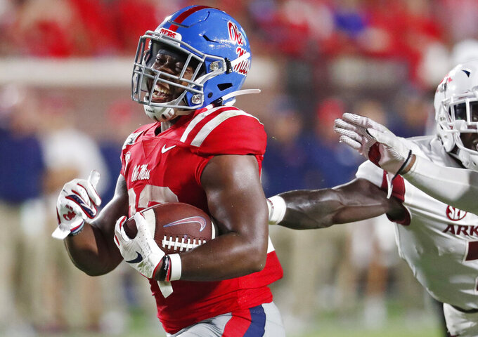 Mississippi running back Scottie Phillips (22) laughs as he runs past Arkansas defenders on his way to a touchdown during the second half of an NCAA college football game Saturday, Sept. 7, 2019, in Oxford, Miss. Mississippi won 31-17. (AP Photo/Rogelio V. Solis)