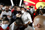 The leader of the ruling SDSM party Zoran Zaev, center right, wearing a mask as he is pose for a selfie after his victory at the North Macedonia general election, in Skopje, early Tuesday, July 16, 2020. A suspected hacking attack caused the site of North Macedonia's electoral commission to crash for hours after polls closed in the country's national elections Wednesday, delaying preliminary results that showed the Social Democrats narrowly leading the center-right opposition.(AP Photo/Boris Grdanoski)