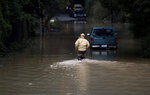 Bruce MacDonell walks through a flooded area of Guerneville, Calif., on Friday, Feb. 15, 2019. In California, rainwater drained from saturated landscapes even as a new system moved into northern areas of the state and more heavy snow fell in the Sierra Nevada.  (AP Photo/Josh Edelson)