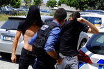 The suspects cover their faces with their shirts as they arrive at the Famagusta courthouse in Paralamni town, Cyprus, Thursday, July 18, 2019. A Cyprus court has ordered 12 Israelis vacationing on the east Mediterranean island nation to remain in police custody for eight days after a 19-year-old British woman alleged that she was raped. (AP Photo/Petros Karadjias)