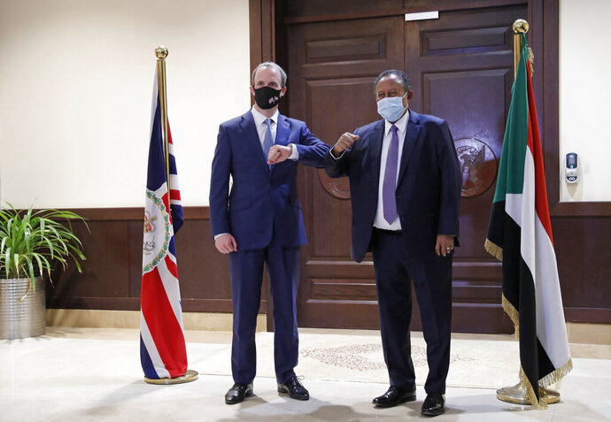Sudanese Prime MInister Abdullah Hamdok, right, bumps elbows with British Foreign Secretary, Dominic Raab in the Cabinet Building, in Khartoum, Sudan, Thursday, Jan. 21, 2021. Raab was in the Sudanese capital Thursday to discuss bilateral relations and tensions along the border with Ethiopia, Sudan's state news agency reported. (AP Photo)