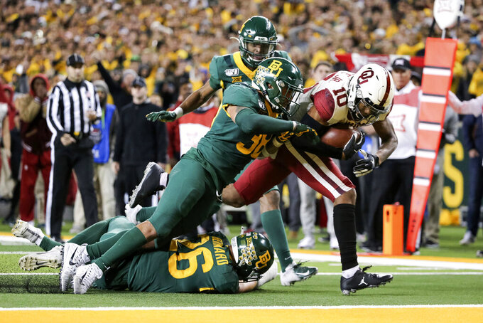 Oklahoma wide receiver Theo Wease (10) scores a 19-yard touchdown as Baylor linebacker Jordan Williams (38) defends during the second half of an NCAA college football game in Waco, Texas, Saturday, Nov. 16, 2019. Oklahoma won 34-31. (AP Photo/Ray Carlin)