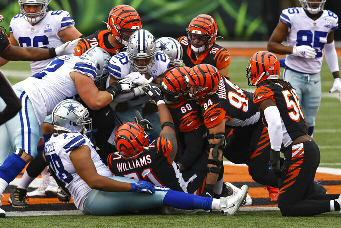 Dallas Cowboys running back Tony Pollard (20) is stopped short of a first down by the Cincinnati Bengals defense in the second half of an NFL football game in Cincinnati, Sunday, Dec. 13, 2020. (AP Photo/Aaron Doster)