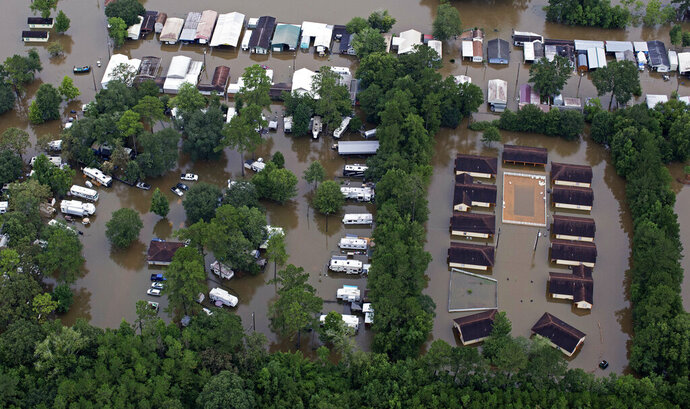 FILE- In this Aug. 13, 2016 aerial photo over Amite, La., flooded homes are seen from heavy rains inundating the region. Memories of an epic flood that caused billions of dollars in damage had Louisiana's capital on edge Friday, July 12, 2019, as Barry gained strength in the Gulf of Mexico. (AP Photo/Max Becherer, File)