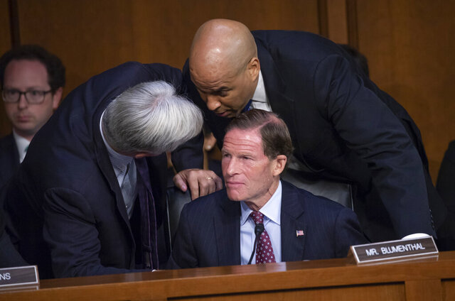 FILE - In this Tuesday, Sept. 4, 2018 file photo, Sen. Sheldon Whitehouse, D-R.I., left, and Sen. Cory Booker, D-N.J., confer with Sen. Richard Blumenthal, D-Conn., seated, as Democrats on the Senate Judiciary Committee appeal to Chairman Chuck Grassley, R-Iowa, to delay the confirmation hearing of President Donald Trump's Supreme Court nominee, Brett Kavanaugh, on Capitol Hill in Washington. On Friday, Oct. 16, 2020, The Associated Press reported on stories circulating online incorrectly asserting that the senators ignored social distancing measures by huddling without face masks during confirmation hearings for Supreme Court nominee Judge Amy Coney Barrett. The photographed situation dates back to 2018, before the coronavirus pandemic began. (AP Photo/J. Scott Applewhite)