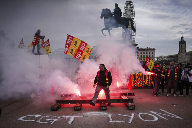 A protester passes by flares during a demonstration in Lyon, central France, Tuesday, Dec. 17, 2019. Workers at the Eiffel Tower, teachers, doctors, lawyers and people from across the French workforce walked off the job Tuesday to resist a higher retirement age, or to preserve a welfare system they fear their business-friendly president wants to dismantle. (AP Photo/Laurent Cipriani)