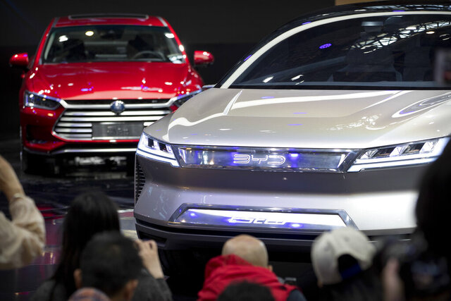 """FILE - In this April 25, 2018, file photo, attendees take photos of the E-SEED electric concept car during a press conference by Chinese automaker BYD at the China Auto Show in Beijing. China is promising more subsidies to shore up plunging electric car sales amid the coronavirus pandemic but set limits that exclude Tesla's made-in-China model. Subsidies and tax breaks that were due to end this year will be extended by two years in response to """"an accumulation of unfavorable factors"""" including the virus, the Finance Ministry said Thursday, April 23, 2020.(AP Photo/Mark Schiefelbein, File)"""