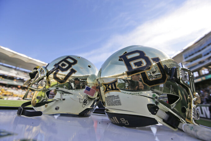 """FILE - In this Dec. 5, 2015, file photo, Baylor helmets on shown the field after an NCAA college football game in Waco, Texas. The NCAA infractions committee said Wednesday, Aug. 11, 2021, that its years-long investigation into the Baylor sexual assault scandal would result in four years probation and other sanctions, though the """"unacceptable"""" behavior at the heart of the case did not violate NCAA rules.(AP Photo/LM Otero, File)"""