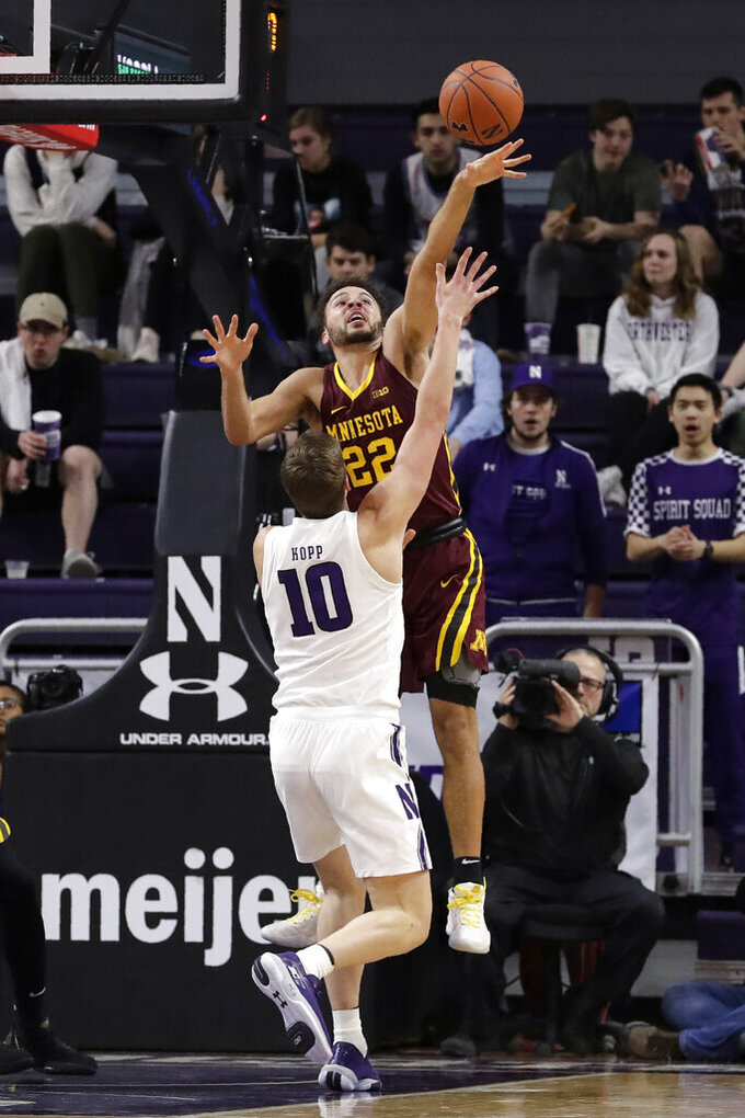 Minnesota guard Gabe Kalscheur, top, blocks a shot by Northwestern forward Miller Kopp during the first half of an NCAA college basketball game in Evanston, Ill., Sunday, Feb. 23, 2020. (AP Photo/Nam Y. Huh)