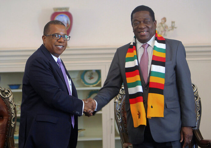 "FILE - In this file photo dated Wednesday, Aug, 15, 2018, United States Ambassador to Zimbabwe Brian Nichols, left, during a courtesy call with Zimbabwean President elect Emmerson Mnangagwa at his official State House in Harare.  Zimbabwe's state-controlled Herald newspaper has reported Monday June 1, 2020, that Nichols has been called to meet with Zimbabwe's foreign minister over comments Sunday by U.S. national security adviser Robert O'Brien that Zimbabwe is one of several ""foreign adversaries"" taking advantage of the protests in the U.S. over the death of George Floyd, a black man who pleaded for air as a police officer pressed a knee into his neck. (AP Photo/Tsvangirayi Mukwazhi, FILE)"