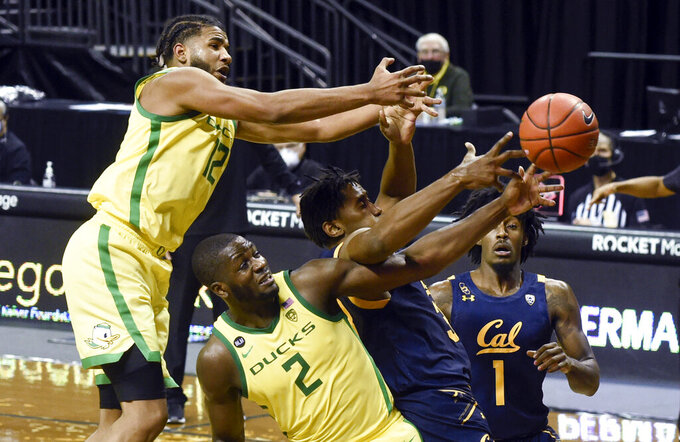 Oregon guard LJ Figuero (12) and forward Eugene Omoruyi (2) vie with California forward D.J. Thorpe (33) and guard Joel Brown (1) for a rebound during the second half of an NCAA college basketball game Thursday, Dec. 31, 2020, in Eugene, Ore. (AP Photo/Andy Nelson)