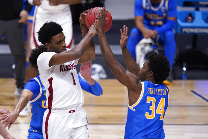 Alabama forward Herbert Jones (1) drives on UCLA guard David Singleton (34) in the first half of a Sweet 16 game in the NCAA men's college basketball tournament at Hinkle Fieldhouse in Indianapolis, Sunday, March 28, 2021. (AP Photo/Michael Conroy)