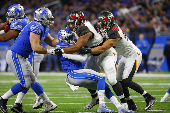 Detroit Lions running back Wes Hills is tackled by Tampa Bay Buccaneers nose tackle Ndamukong Suh (93) and linebacker Carl Nassib during the first half of an NFL football game, Sunday, Dec. 15, 2019, in Detroit. (AP Photo/Paul Sancya)