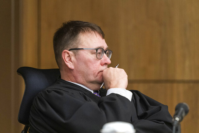 Superior Court Judge Eric Aarseth listens to arguments over an effort to recall Alaska Gov. Mike Dunleavy Friday, Jan. 10, 2020, in Anchorage, Alaska. Judge Aarseth ruled that an effort to recall Republican Gov. Mike Dunleavy may proceed, a decision that is expected to be appealed. The decision followed arguments in the case and came two months after Gail Fenumiai, director of the state Division of Elections, rejected a bid to advance the recall effort. (Loren Holmes/Anchorage Daily News via AP)