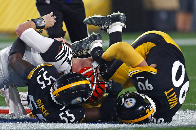 Cincinnati Bengals quarterback Andy Dalton (14) is sacked by Pittsburgh Steelers linebacker Devin Bush (55) and T.J. Watt (90) during the first half of an NFL football game in Pittsburgh, Monday, Sept. 30, 2019. (AP Photo/Tom Puskar)