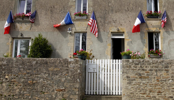 French and U.S. flags decorate a house front near Omaha Beach, Thursday, June 4, 2020, in Saint-Laurent-sur-Mer, Normandy, France. France has avoided echoing U.S. President Donald Trump's criticism of Beijing's handling of the coronavirus, but legislators applauded Foreign Minister Jean-Yves Le Drian mid July 2020 when he condemned abuses of minority Uighurs in China's northwest. (AP Photo/Virginia Mayo, File)