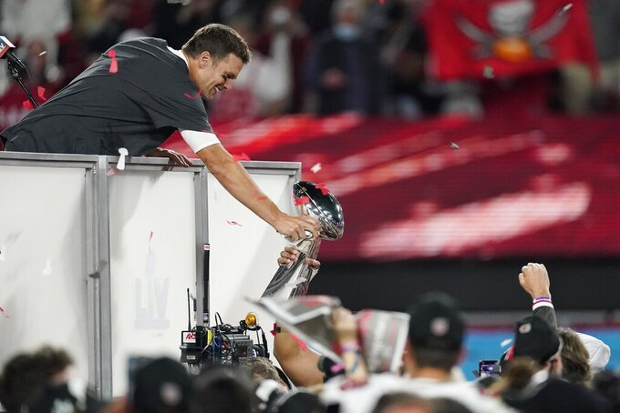 Tampa Bay Buccaneers quarterback Tom Brady grabs the Vince Lombardi trophy after defeating the Kansas City Chiefs in the NFL Super Bowl 55 football game Sunday, Feb. 7, 2021, in Tampa, Fla. The Buccaneers defeated the Chiefs 31-9 to win the Super Bowl. (AP Photo/Ashley Landis)