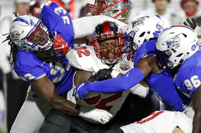 Western Kentucky running back D'Andre Ferby (32) is stopped by Middle Tennessee defenders Malik Manciel (93), Luke Harris, second from right, and Rosheem Collins (96) in the first half of an NCAA college football game Friday, Nov. 2, 2018, in Murfreesboro, Tenn. (AP Photo/Mark Humphrey)