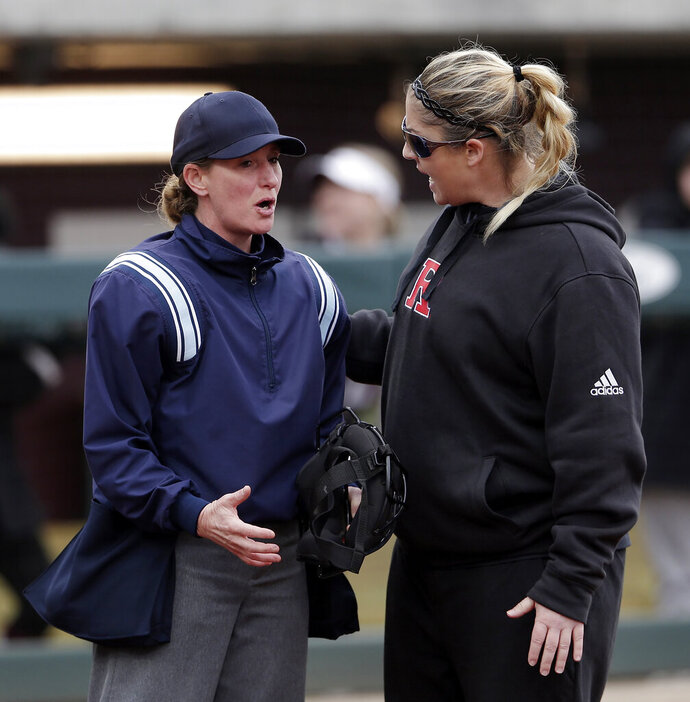 FILE - In this Feb. 16, 2019, file photo, Rutgers head coach Kristen Butler, right, argues a call with the home plate umpire during an NCAA college softball game against Texas A&M in College Station, Texas. On Tuesday, June 2, 2020, the results of a seven-month investigation into allegations of physical and emotional abuse in the Rutgers University softball program has found examples of inappropriate behavior but stops short of imposing discipline on the coaches. The probe released followed allegations that Butler and assistant coach Marcus Smith, her husband, fostered a climate of fear, intimidation and abuse. (AP Photo/ Michael Wyke, File)