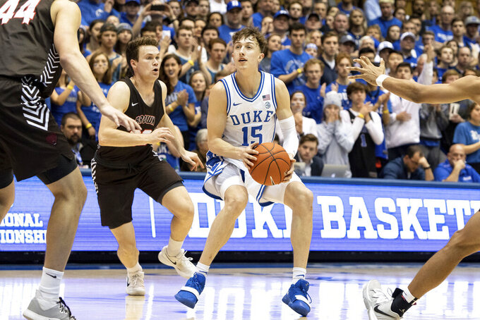 Duke's Alex O'Connell, right, handles the ball ahead of Brown's Zach Hunsaker, left, during the second half of an NCAA college basketball game in Durham, N.C., Saturday, Dec. 28, 2019. (AP Photo/Ben McKeown)