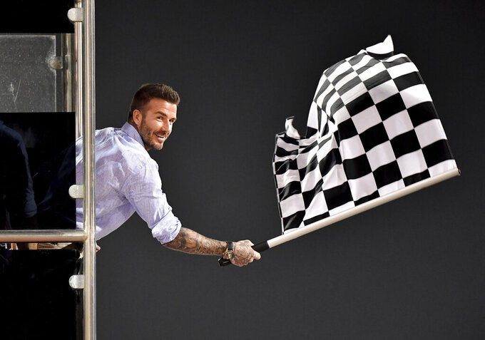 Former British football player David Beckham waves the checkered flag as Mercedes driver Lewis Hamilton of Britain crosses the finish line during during the Formula One Bahrain Grand Prix at the Sakhir circuit in Bahrain, Sunday, March 31, 2019. (Andrej Isakovic, Pool Photo via AP)