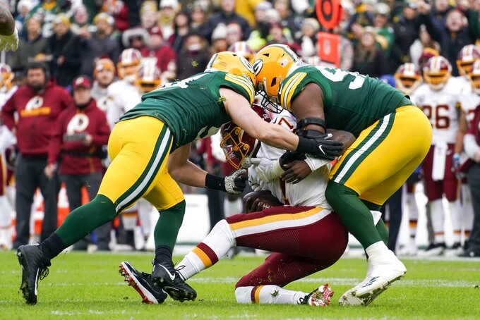 Washington Redskins' Dwayne Haskins is sacked by Green Bay Packers' Kyler Fackrell and Kenny Clark during the first half of an NFL football game Sunday, Dec. 8, 2019, in Green Bay, Wis. (AP Photo/Morry Gash)