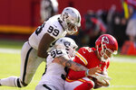 Kansas City Chiefs quarterback Patrick Mahomes (15) is sacked by Las Vegas Raiders defensive end Maxx Crosby (98) and defensive end Arden Key (99) during the second half of an NFL football game, Sunday, Oct. 11, 2020, in Kansas City. (AP Photo/Charlie Riedel)
