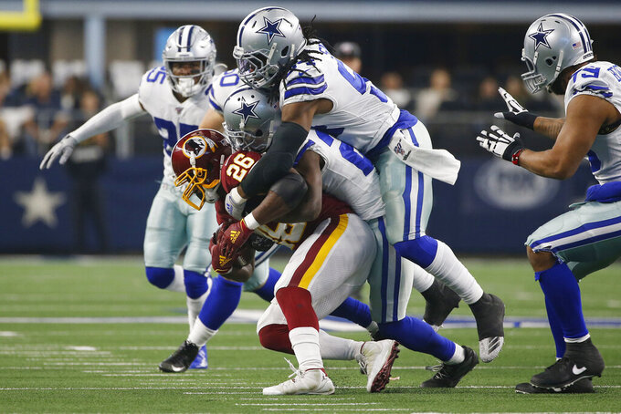 Washington Redskins running back Adrian Peterson (26) is stopped by Dallas Cowboys defenders on a run during the first half of an NFL football game in Arlington, Texas, Sunday, Dec. 15, 2019. (AP Photo/Ron Jenkins)