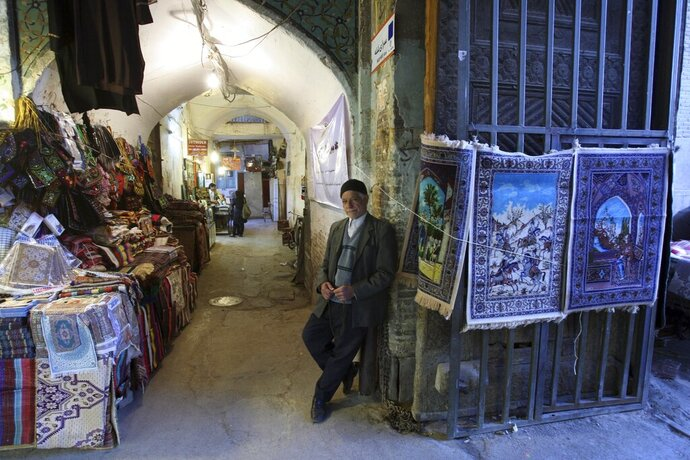 """FILE - In this April 7, 2011 file photo, an Iranian vendor stands in front of his goods at Qeisariyyeh old bazaar, in Imam Square in the city of Isfahan, Iran. The ancient and rich cultural landscape of Iran has become a potential U.S. military target as Washington and Tehran lob threats and take high-stakes steps toward a possible open conflict. President Donald Trump tweeted Saturday, Jan. 4, 2020, that if Iran targets any American assets to avenge the killing of a top Iranian general, the U.S. has 52 Iranian sites it will hit, including ones """"important to Iran & Iranian culture."""