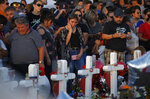 People visit a makeshift memorial at the scene of a mass shooting at a shopping complex, Tuesday, Aug. 6, 2019, in El Paso, Texas. (AP Photo/John Locher)