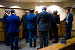 """FILE - In this Monday, Jan. 8, 2018 file photo, attorneys meet with Genesee District Judge Jennifer J. Manley as preliminary examination begins in the cases of four defendants, all former or current officials from the Michigan Department of Environmental Quality at Flint District Court in downtown Flint, Mich. Michigan's attorney general in 2016 promised to investigate the Flint water scandal """"without fear or favor"""" and pledged that state regulators would be locked up for fudging data and misleading the public about lead in the poor city's pipes. Yet three years later, no one is behind bars. (Jake May/The Flint Journal-MLive.com via AP)"""
