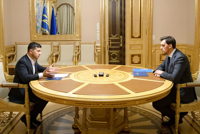 In this photo provided by the Ukrainian Presidential Press Office, Ukrainian President Volodymyr Zelenskiy, left, talks with Ukraine's Prime Minister Oleksiy Honcharuk in Kyiv, Ukraine, Friday, Jan.17, 2020. Honcharuk earlier submitted his resignation to parliament following a leaked audio recording which suggested he had criticised the president. (Ukrainian Presidential Press Office via AP)