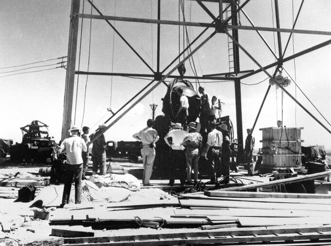 FILE - In this July 6, 1945, file photo, scientists and other workers rig the world's first atomic bomb to raise it up onto a 100-foot tower at the Trinity bomb test site near Alamagordo, N.M. A bipartisan group of lawmakers is renewing the push to expand a federal compensation program for radiation exposure following uranium mining and nuclear testing carried out during the Cold War. Advocates have been trying for years to bring awareness to the lingering effects of nuclear fallout surrounding the Trinity Site in southern New Mexico and on the Navajo Nation, where more than 30 million tons of ore were extracted over decades to support U.S. nuclear activities. (AP Photo/File )