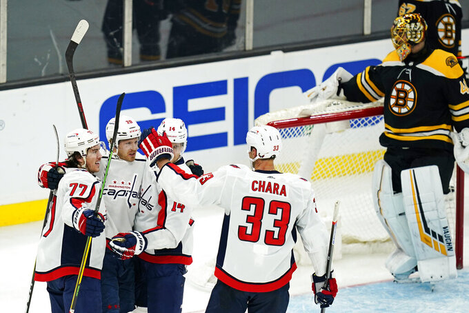 Washington Capitals center Lars Eller (20) is congratulated by teammates after his goal against Boston Bruins goaltender Tuukka Rask, rear right, during the third period of an NHL hockey game, Wednesday, March 3, 2021, in Boston. From left are Capitals Washington Capitals T.J. Oshie (77), Ellers, Richard Panik (14) and Zdeno Chara (33). (AP Photo/Charles Krupa)