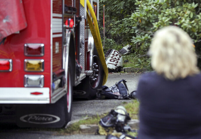 A bystander looks at the wreckage of a single-engine plane behind a home on Minchin Drive, Saturday, Sept. 15, 2018, in Woburn, Mass. Officials said Dr. Michael Graver and Jodi Cohen were killed in the crash. The plane had departed from Republic Airport in Farmingdale, N.Y.,  and was en route to Laurence G. Hanscom Field in Bedford, Mass., about four miles from the crash site. (Nicolaus Czarnecki/The Boston Herald via AP)