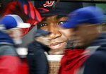 FILE - In this Oct. 1, 2016, file photo, fans at walk past a photograph of Boston Red Sox's David Ortiz before a baseball game against the Toronto Blue Jays at Fenway Park in Boston. Ortiz was back in Boston for medical care after authorities said the former Red Sox slugger affectionately known as Big Papi was ambushed by a gunman at a bar in his native Dominican Republic. A plane carrying the 43-year-old retired athlete landed Monday night, June 10, 2019, after a flight from the Dominican Republic, the team said. (AP Photo/Michael Dwyer, File)