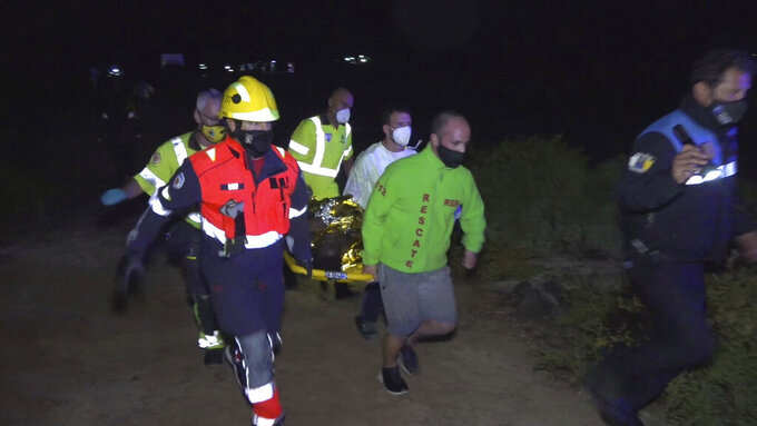 Emergency service members carry the body of a migrant after been rescued at the island of Lanzarote in the Spain's Canary Islands on Friday, Jun 18, 2021. Spanish authorities say four people have died including a child after a migrant boat believed to be carrying 45 passengers capsized near Spain's Canary Islands. The boat was approaching Órzola on the island of Lanzarote on Thursday night when it flipped over a few meters (yards) from shore, throwing the passengers into the water. (Europa Press via AP)